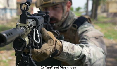 Slow motion closeup of soldier and his military gun during...