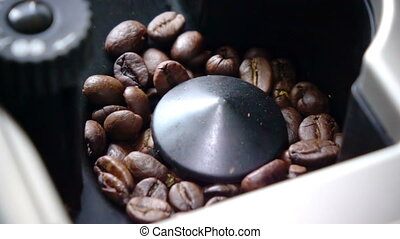 Slow motion ,coffee grains are milled in the coffee machine...