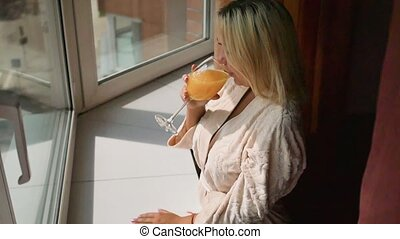 Slow motion. Cute young woman enjoying a pleasant morning by the window