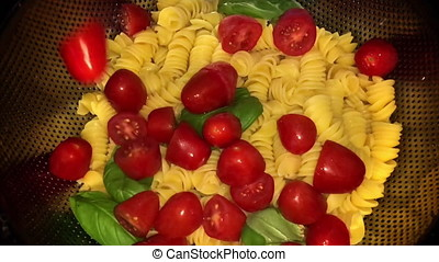 Slow Motion Dropping Tomato On Pasta And Basil. At the heart...