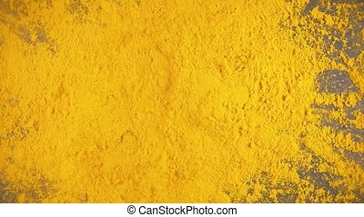 Slow motion turmeric powder dry spice drops on a gray background from under the camera
