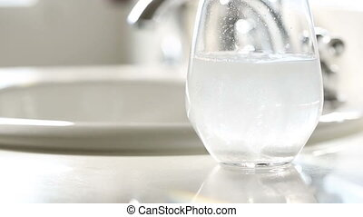 Slow Motion Effervescent Cold Tablets Dropping Into a Water...