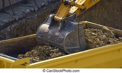Slow motion - Excavator loading soil on a dump truck....