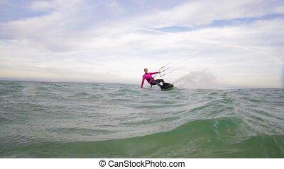 SLOW MOTION: Female kite-boarder riding and splashing water...