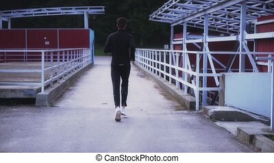 Slow motion. Fit athlete running on small bridge. Background...