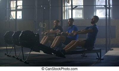 Slow motion: Fitness friends training on row ergometer machine at cross gym