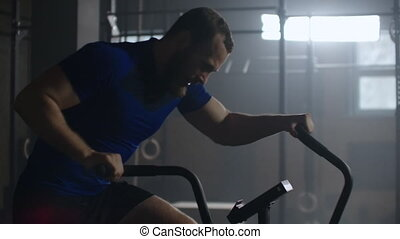 SLow motion: Fitness man on bicycle doing spinning at gym. Fit young female working out on gym bike