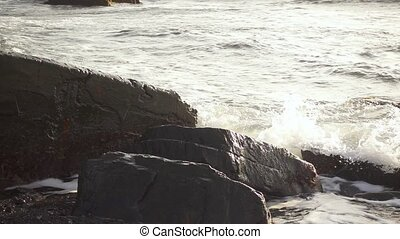Slow Motion foam from the wave crashed on the boulder soars...