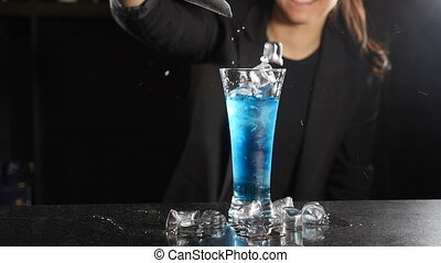 Slow motion footage Ice cubes falling into glass full of blue liquid with splashes. Close up. Female bartender making cocktail on dark background. Full hd
