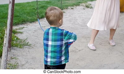 Slow motion footage of barefoot toddler boy carrying plastic...