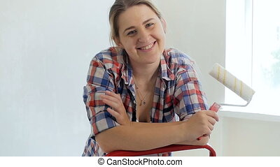 Slow motion footage of beautiful smiling woman holding paint roller