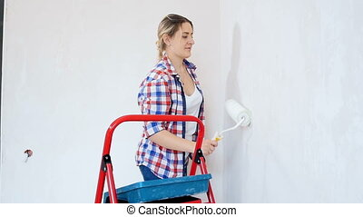 Slow motion footage of beautiful smiling woman painting walls with paint roller