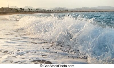 Slow motion footage of beautiful sunset over sea waves on golden beach