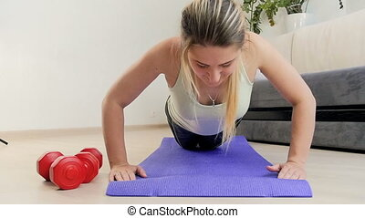 Slow motion footage of beautiful young woman doing push ups...