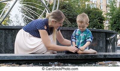 Slow motion footage of beautiful young mother with her toddler boy relaxing at fountain in park