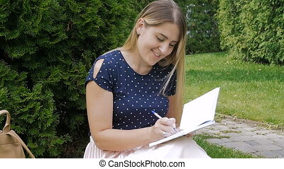 . Slow motion footage of beautiful young woman sitting in park on grass and writing a diary