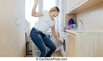 Slow motion footage of cheerful young woman dancing and singing while doing laundry in house