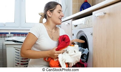 Slow motion footage of cheerful young woman throwing big heap of clothes in the air at laundry