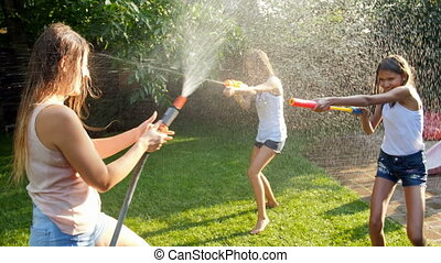 Slow motion footage of children playing with water guns and...