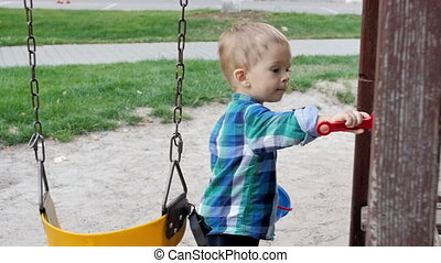 Slow motion footage of cute 2 years old boy playing with...