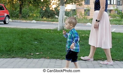 Slow motion footage of cute barefoot toddler boy walking...