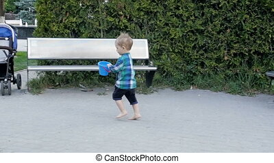 Slow motion footage of cute barefoot toddler boy running on...