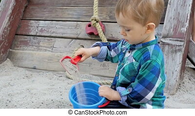 Slow motion footage of cute blonde toddler boy digging sand...