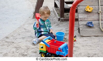 Slow motion footage of cute toddler boy playing with toys in...