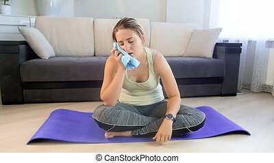 Slow motion footage of exhausted sweaty woman sitttiing on fitness mat at home after exercising