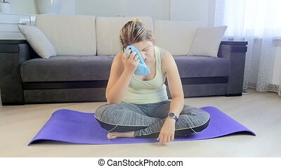 Slow motion footage of exhausted young woman with towel after workout at home