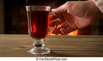 Slow motion footage of female hand taking mug with mulled...