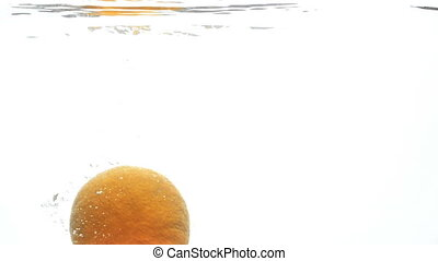 Slow motion footage of fresh ripe orange falling in cold...