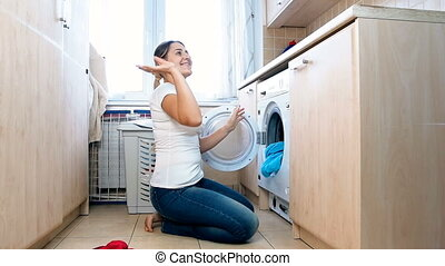 Slow motion footage of happy cheerful housewife throwing clothes clean clothes at laundry
