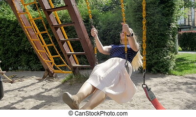 Slow motion footage of happy smiling girl riding on swing at...