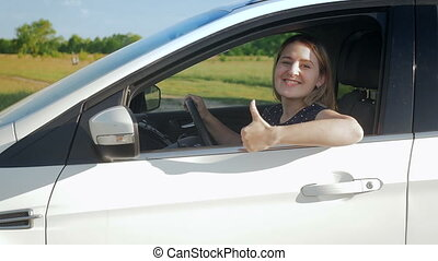 Slow motion footage of happy smiling woman driving car at...