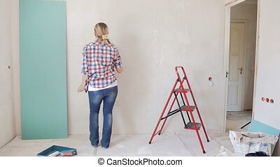 Slow motion footage of happy young woman painting wall and...