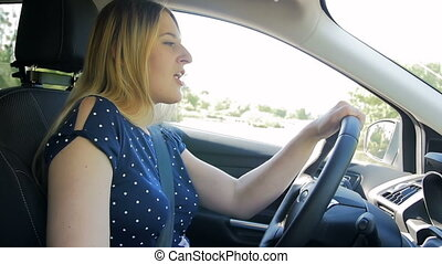 Slow motion footage of happy young woman driving car and...
