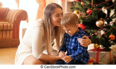 Slow motion footage of laughing toddler boy playing with mother and having fun under Christmas tree at morning