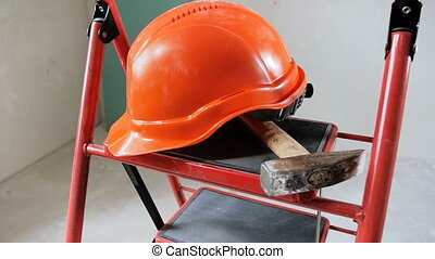 Slow motion footage of red hardhat and hammer lying on...