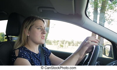 Slow motion footage of stressed woman driving car and...