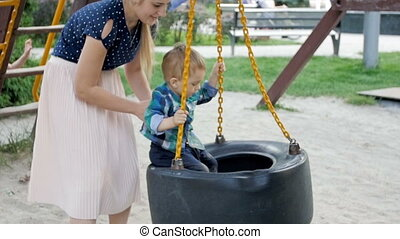 Slow motion footage of toddler boy spinning on chain swing...
