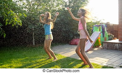 Slow motion footage of two laughing teenage girls dancing and jumping under warm summer rain at backyard
