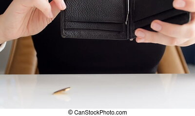 SLow motion footage of woman shaking her wallet and searching for money. One coin falling out on table