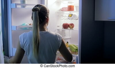 Slow motion footage of young beautiful woman opens refrigerator at night and takes yoghurt