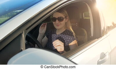 Slow motion footage of young female driver wearing...