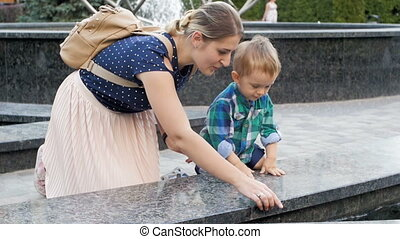 Slow motion footage of young mother showing fountain in park...