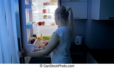 Slow motion footage of young sleepy woman in pajamas taking food from refrigerator at night
