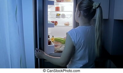 Slow motion footage of young sleepy woman taking food from refrigerator at night