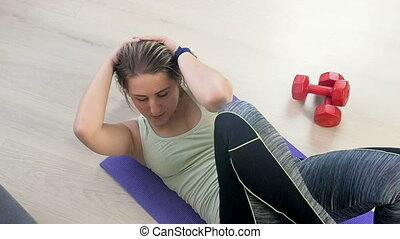 Slow motion footage of young tired woman exercising on fitness mat at home