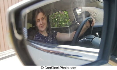 Slow motion footage of young woman adjusting car side view...